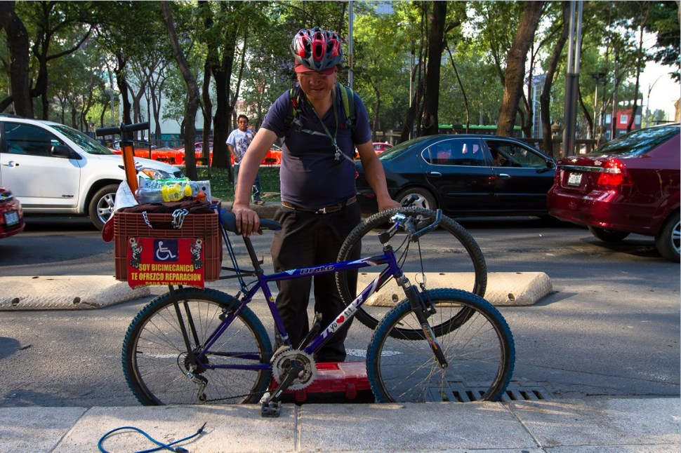 Persona ofrece servicios de reparación de bicicletas sobre Paseo de la Reforma (NTX)