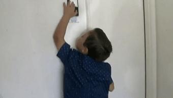 Salvatore Cicalese alcanzando el botón para abrir las puertas del garage.