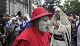 Personajes enmascarados y vestidos de rojo salen de la Iglesia de San Pablo Apóstol, en Cuajimalpa. (Getty Images)
