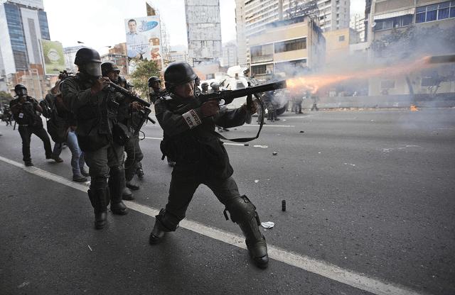 La Guardia Nacional Bolivariana de Venezuela lanza gases a los opositores durante una marcha. (AP)