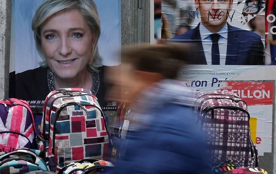 Una mujer recorre los carteles oficiales de los candidatos para la elección presidencial francesa de 2017 (Reuters)
