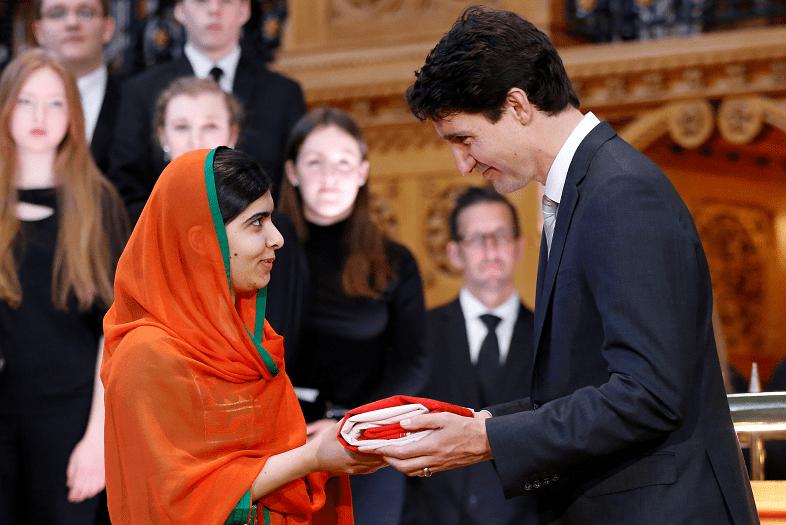 El primer ministro de Canadá, Justin Trudeau, otorga a la ganadora del Premio Nobel de Paz Malala Yousafzai una bandera canadiense durante una ceremonia en el Parlamento en Ottawa (Reuters)