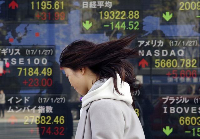 Un peatón camina frente a un tablero con información de los mercados nipones. (AP, archivo)