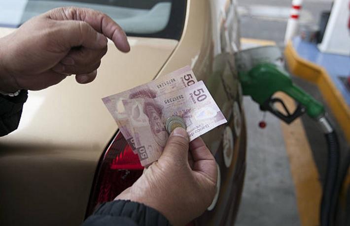 Un cliente se prepara para pagar después de recibir su tanque lleno de gasolina en una estación de Pemex en la Ciudad de México, México (Getty Images)