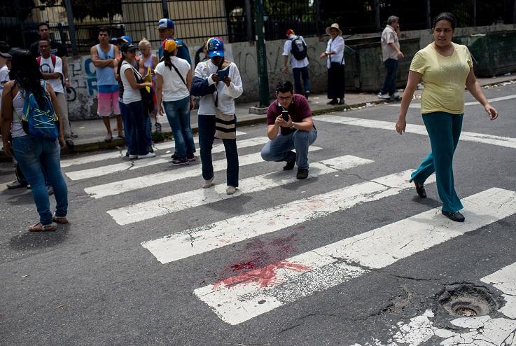 La mancha de sangre del joven de 17 años que resultó herido durante una concentración de la oposición en Caracas (EFE)