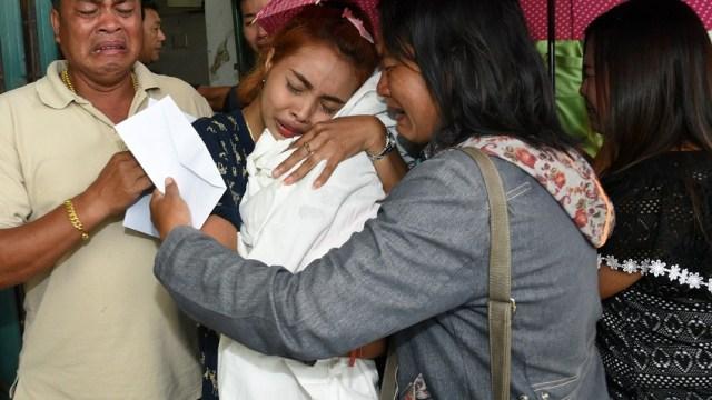 Jiranuch Trirat sostiene el cuerpo de su hija de 11 meses de edad, quien fue asesinada por su padre, quien difundió el asesinato en Facebook (Reuters)