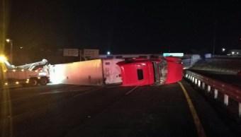 Un tráiler vuelca en la autopista México-Querétaro en el kilómetro 207+300, a la entrada del municipio de Querétaro, debido al piso mojado y al exceso de velocidad; el chofer resulta lesionado . (Noticieros Televisa)