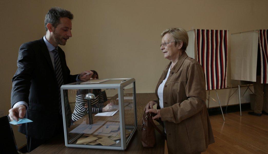 Un trabajador electoral comprueba la tarjeta de un votante en la segunda vuelta de la elección presidencial francesa (Reuters)