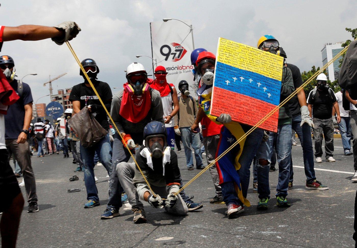 Manifestantes lanzan tarros con excremento a los miembros de seguridad de Venezuela. (Reuters)