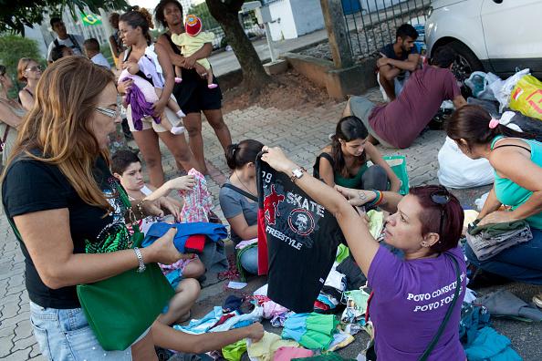 Mujeres brasileñas obtienen ropa en tianguis