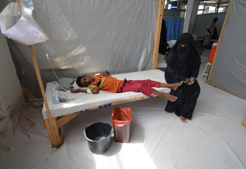 Una mujer se sienta al lado de su hijo infectado con cólera (Reuters)