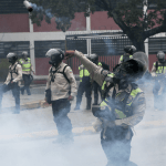 Policias venezolanos lanzan gases lacrimogenos a opositores