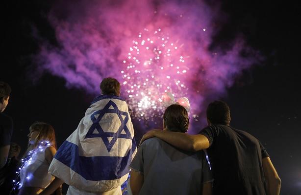 Israelíes sostienen banderas de su país mientras observan fuegos artificiales (EFE)