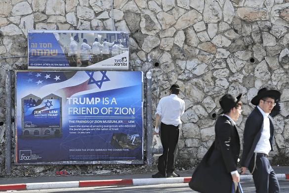 Judíos ultraortodoxos caminan frente a un cartel que da la bienvenida a Trump en Jerusalén