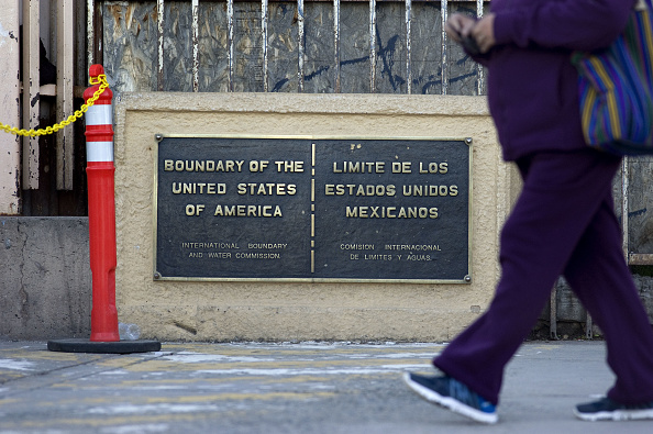 Una persona camina soreb la fronteta de Mexico y Estados Unidos