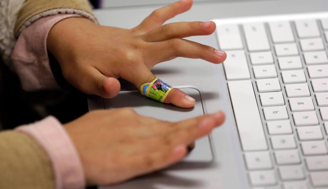 Manos de un niño sobre el teclado de una computadora