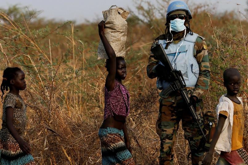 Un soldado de la ONU está de guardia mientras los niños caminan al norte de Sudán del Sur (Reuters)