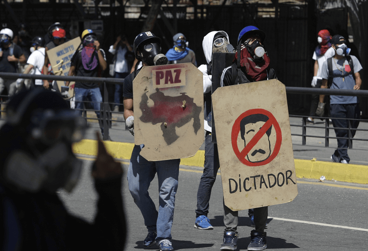 Opositores al gobierno de Maduro se protegen con escudos durante protestas en Caracas