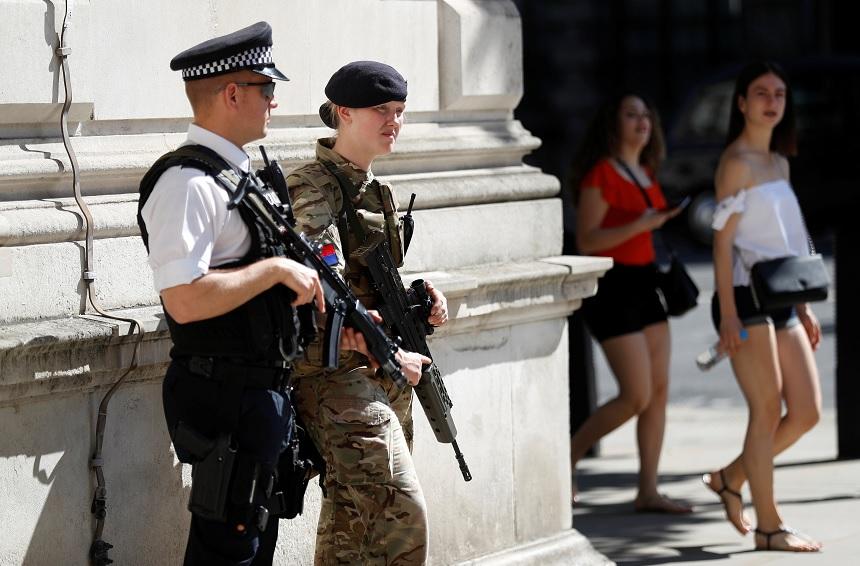 Los turistas pasan por delante de un soldado y un oficial de policía armado en Londres, Gran Bretaña (Reuters)
