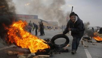 Un manifestante utiliza un neumático en llamas para construir una barricada durante una protesta en Johannesburgo, Sudáfrica (EFE)