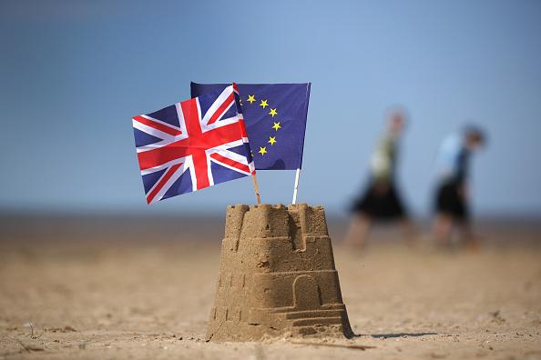 Banderas de Reino Unido y Union Europea sobre castillo de arena