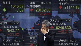 Un peatón pasa frente a un tablero de la Bolsa de Tokio