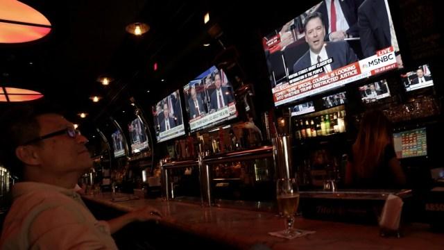 Un hombre mira una televisión mostrando el testimonio del ex director del FBI James Comey (Reuters)