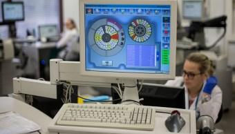medicos toman muestras y las registran en una computadora