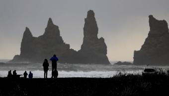 La gente camina en la playa negra en Vik, Islandia, cerca del volcán Katla