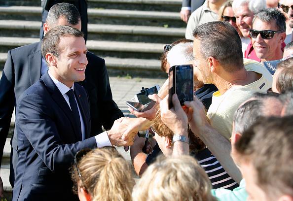 El presidente francés, Emmanuel Macron, da la mano a los simpatizantes a la salida de la mesa de votación (Getty Images)