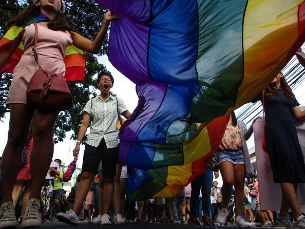 Un grupo de personas extiende una bandera gay durante una marcha en Manila, Filipinas (Getty Images)