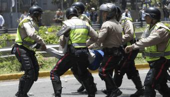 Policías venezolanos cargan a un manifestante durante las protestas