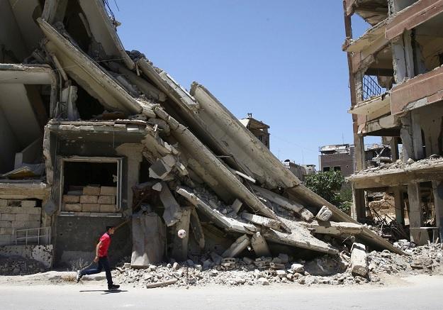 Un joven juega frente a edificios dañados por bombardeos en Damasco (Reuters)