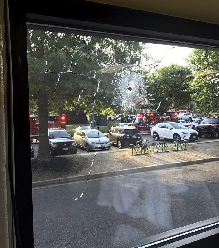 El personal de emergencia se ve a través de una ventana con un agujero de bala en Alexandria, Virginia (AP)