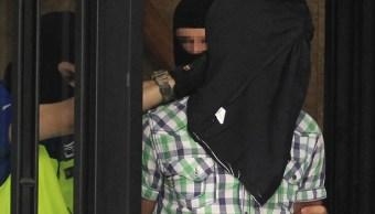 Agentes de la Policía Nacional trasladan a uno de los tres presuntos yihadistas marroquíes detenidos esta madrugada en Madrid (EFE)