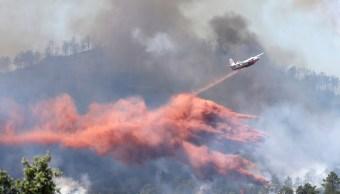 Avión de bomberos descarga retardante sobre incendio