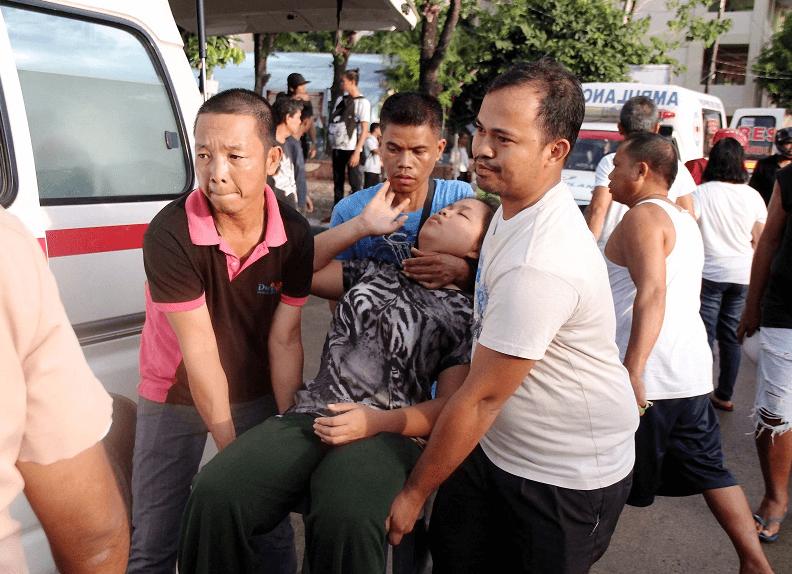 Ciudadanos filipinos socorren a una persona lesionada a causa del terremoto