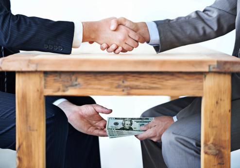 Hombres se entregan dinero por debajo de la mesa