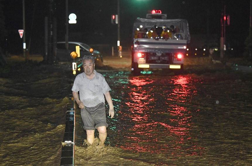Un hombre camina a través de una calle inundada en Asakura, Japón (Reuters)