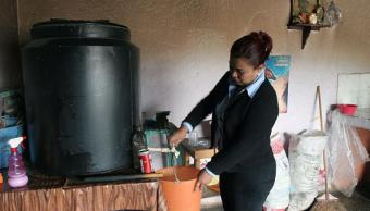 Una mujer saca agua de un tanque en iztapalapa