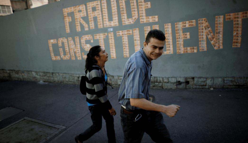Venezolanos caminan frente a un letrero contra la Asamblea