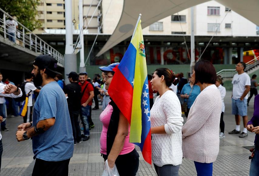 Una mujer sostiene una bandera nacional mientras está en línea junto con otros para emitir su voto durante un plebiscito no oficial contra el gobierno del presidente de Maduro (Reuters)
