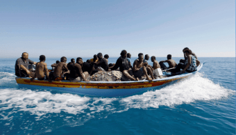Migrantes viajan en un bote luego de ser rescatados