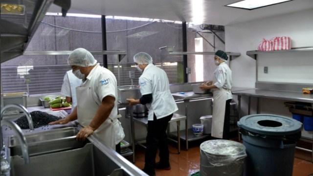 varias personas trabajan en una cocina de restaurante
