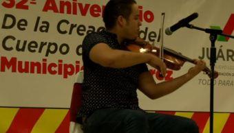 un hombre toca una melodia con violin a bomberos
