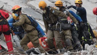 Equipo de rescate israelí saca un cuerpo de entre los escombros