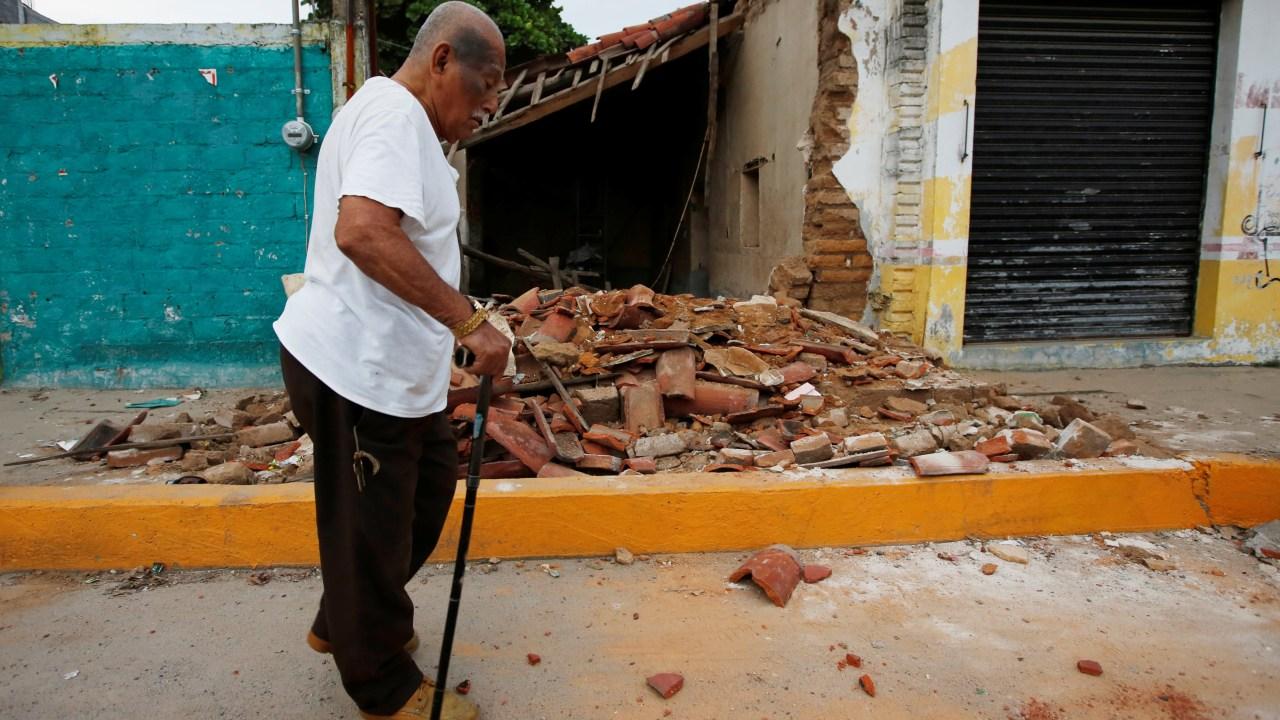 Hombre camina frente a una vivienda destruida por el sismo