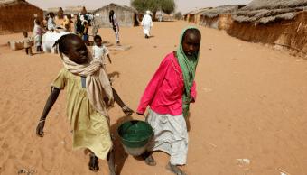 Dos ninas sudanesas cargan agua en un campo de refugiados