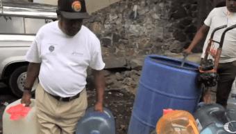 Vecinos Xochimilco acarrean botellones con agua a un mes del sismo 19S