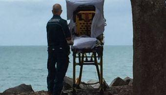 La fotografía de unos paramédicos cumpliendo el deseo de una paciente sujeta a cuidados paliativos mirando al mar se ha vuelto viral en Australia. (Queensland Ambulance Service)